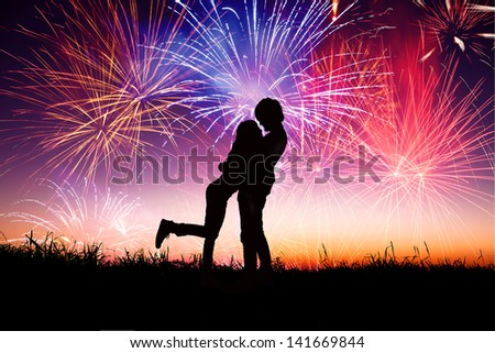 loving young couple with fireworks background - stock photo