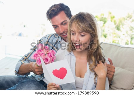 Loving young couple with flowers and greeting card sitting at home - stock photo
