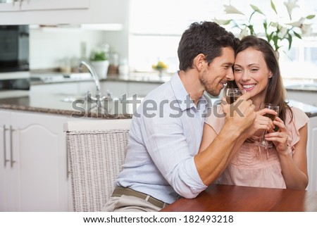 Loving young couple with wine glasses sitting in the kitchen at home - stock photo