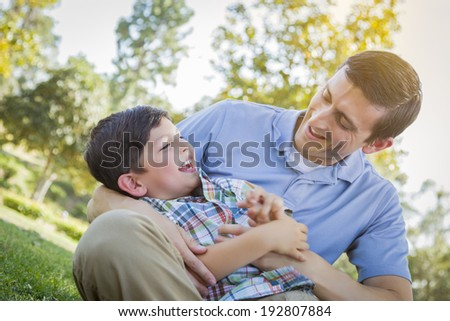 Loving Young Father Tickling Son in the Park. - stock photo