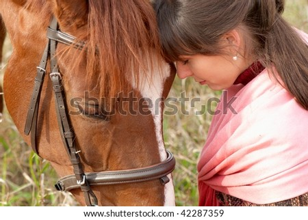 Loving young girl with her horse - stock photo