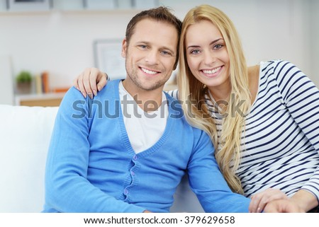 Loving young married couple relaxing together at home sitting arm in arm on a sofa smiling at the camera