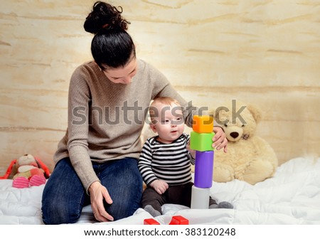 Loving Young Mom and her Cute Baby Boy Playing with Colored Plastic Blocks at Home. - stock photo