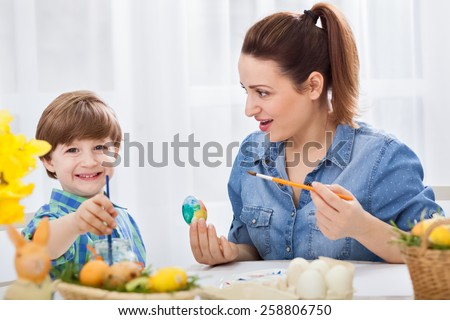 Loving young mother and her child painting easter eggs - stock photo