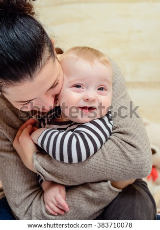 Loving young mother with her young baby in her arms cuddling and nuzzling him tenderly as he smiles at the camera - stock photo