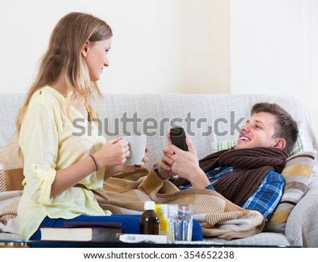 Loving young wife taking care of sick husband lying on sofa at home
