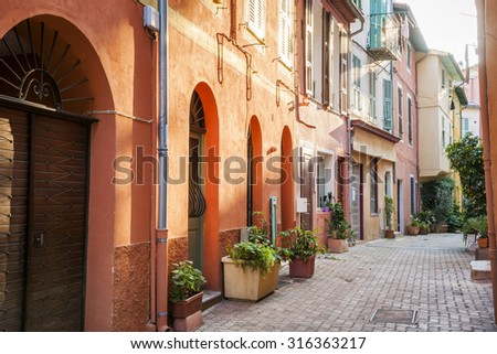 Low afternoon sun illuminating narrow old street with colorful painted buildings and green potted plants in medieval town Villefranche-sur-Mer on French Riviera, France.
