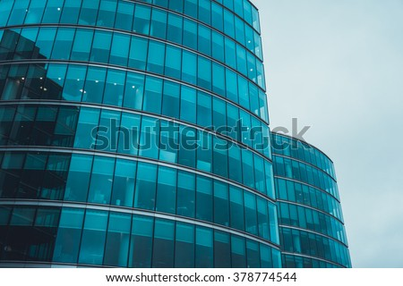 Low Angle Architectural Exterior of Modern Commerical Office Building with Round Glass Facade in Financial District on Overcast Day with Cloudy Gray Sky and Copy Space, London, England - stock photo