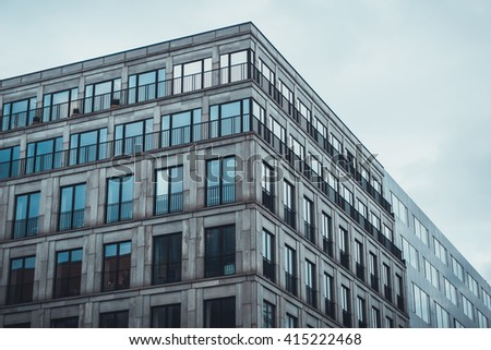 Low Angle Architectural Exterior of Modern Low Rise Residential Apartment or Condominium Building with Sliding Glass Doors in Urban City Setting with Overcast Sky - stock photo