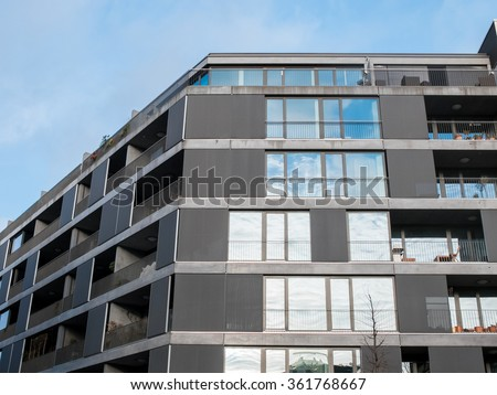 Low Angle Architectural Exterior View of Low Rise Modern Residential Apartment Building with Balconies and Large Windows with Gray Facade