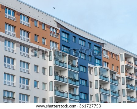 Low Angle Architectural Exterior View of Modern Colorful Residential Apartment Building with Balconies and Blue Sky in Background