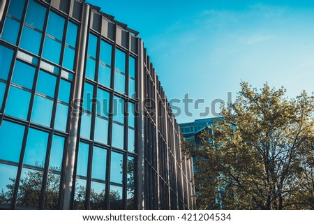 Low Angle Architectural View of Low Rise Modern Office Building in Urban Setting with Green Deciduous Trees on Sunny Day with Blue Sky in Munich, Germany - stock photo