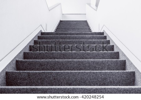 Low angle black and white picture of empty indoor steps - stock photo