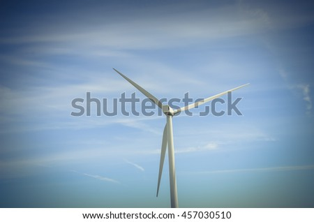 Low angle, close-up view a wind turbine tower again cloud blue sky on a wind farm at Ellensburg, Washington, US. Clean, sustainable, renewable energy concept. Alternative energy source from wind power