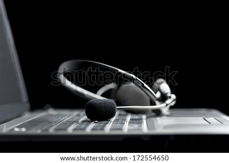 Low angle close up view of a headset lying on the keyboard of an open a laptop computer conceptual of hands free communication, client services or company support through a call center - stock photo