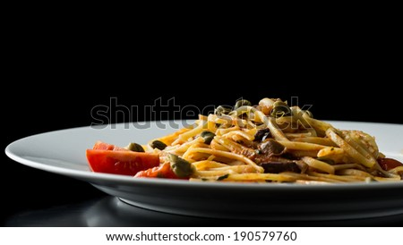 Low angle close up view of a plate of delicious savory Italian bavette pasta with tomatoes, olives and capers against a dark background with copyspace. - stock photo