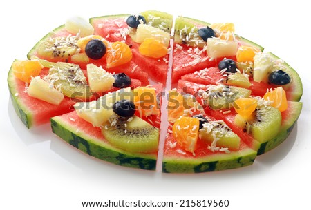 Low angle close up view of a sliced exotic tropical fruit watermelon pizza topped with kiwifruit, blueberries, orange, pineapple, and sprinkled with desiccated coconut for a fun dessert at a party - stock photo