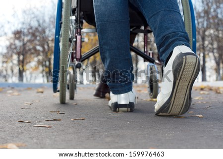 Low angle close up view of the feet of a person pushing a wheelchair along a tarred street