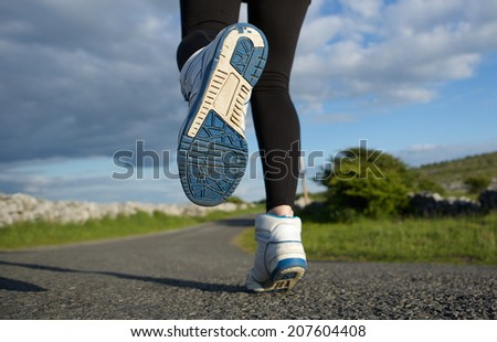 Low angle close up woman running in sneakers on road - stock photo