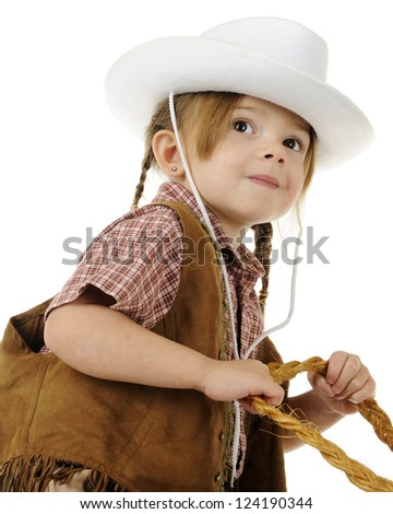 Low angle, closeup image of a preschool cowgirl with her hands on rope reigns.  On a white background. - stock photo