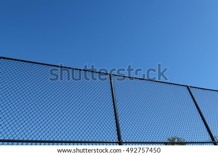 Low angle looking up at black chain link fence on a beautiful day.