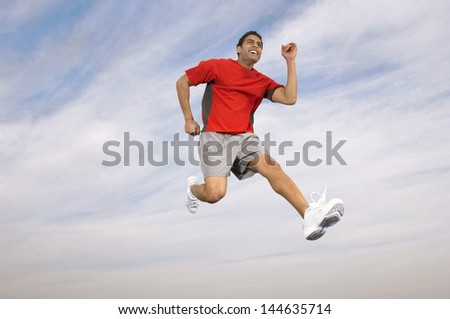 Low angle of a male athlete running midair against the sky and clouds - stock photo