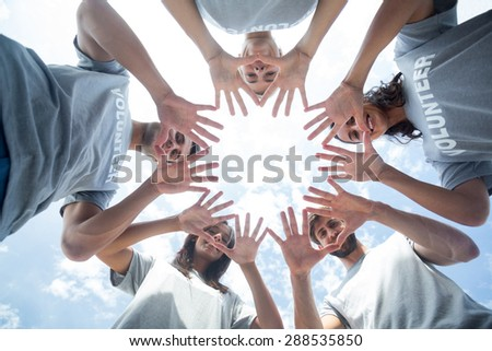 Low angle of happy volunteers playing with their hands - stock photo