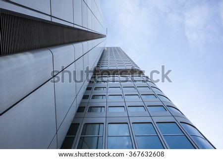Low angle perspective of the exterior facade of a modern office block or commercial skyscraper with curved corners against a hazy blue sky in Frankfurt, Germany - stock photo