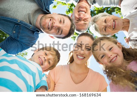 Low angle portrait of an extended family forming huddle in the park - stock photo