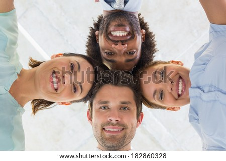 Low angle portrait of business team with heads together forming a huddle