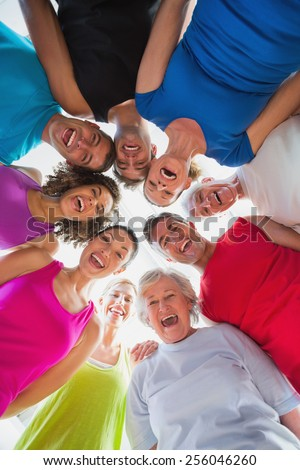Low angle portrait of cheerful people forming huddle at gym - stock photo