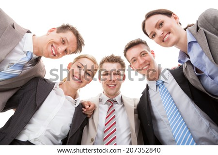 Low angle portrait of confident business team making huddle against white background