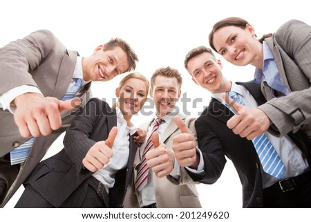 Low angle portrait of confident business team showing thumbs up against white background - stock photo