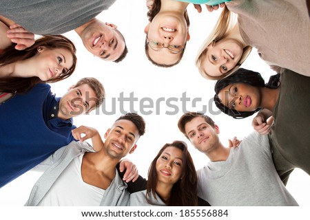 Low angle portrait of confident college students forming huddle over white background - stock photo