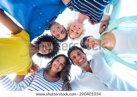 Low angle portrait of confident creative team forming huddle - stock photo