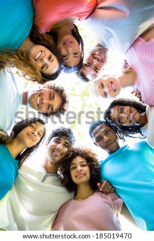Low angle portrait of confident friends forming huddle - stock photo