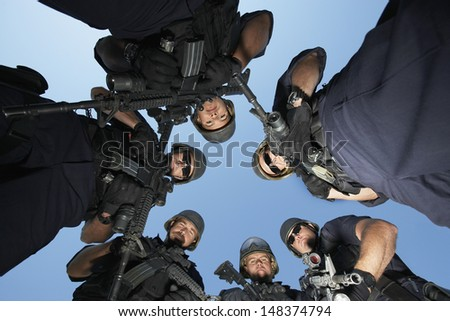 Low angle portrait of confident policemen with guns standing against sky - stock photo