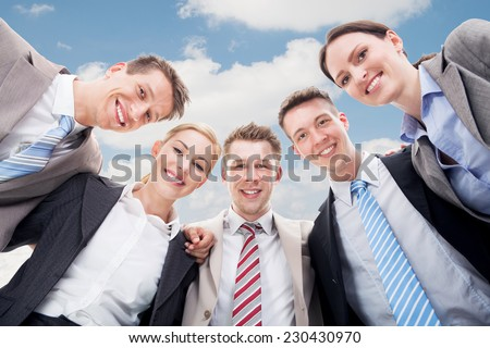 Low angle portrait of happy businesspeople making huddle against cloudy sky
