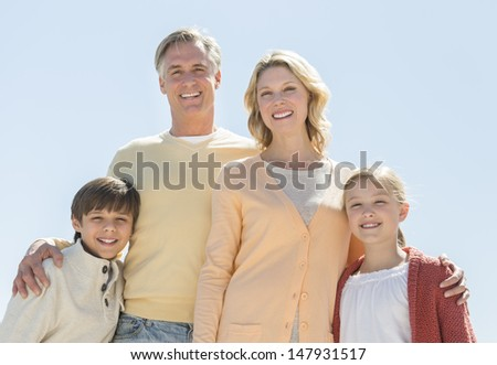 Low angle portrait of happy family of four standing against clear blue sky