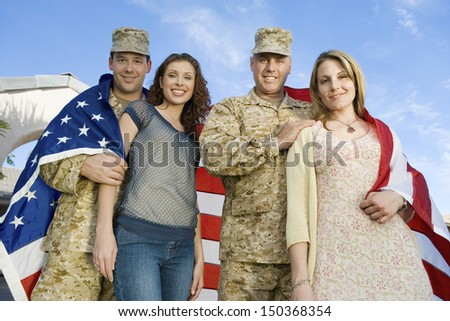 Low angle portrait of happy military couples wrapped in American flag against sky - stock photo