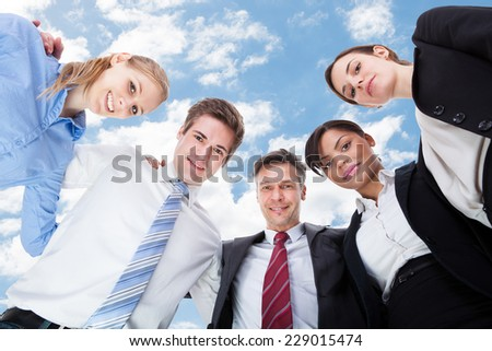 Low angle portrait of multiethnic business people forming huddle against sky