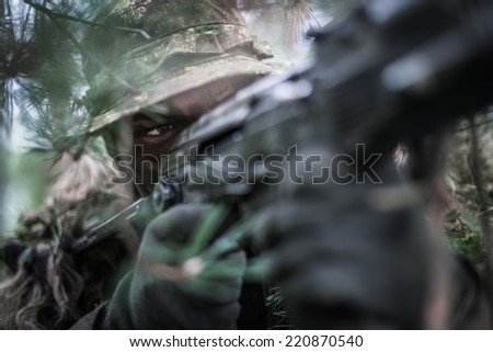 low angle  portrait of special forces soldier wearing boonie hat, hidden behind trees. - stock photo