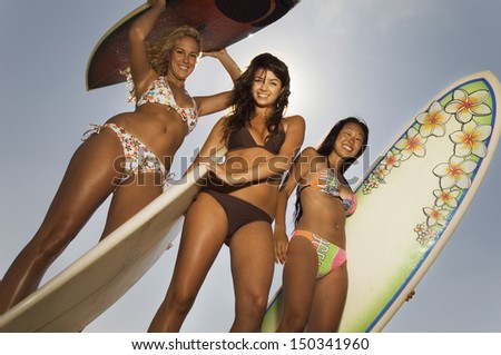 Low angle portrait of young friends in bikinis carrying surfboards against sky - stock photo