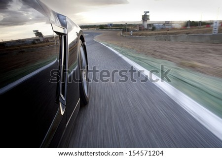 Low angle shot from the side of a car driving fast in a racetrack. Car running in a racetrack.