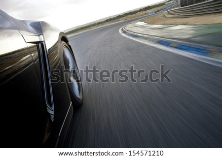 Low angle shot from the side of a car driving in a curve in a racetrack. Car running in a racetrack. - stock photo