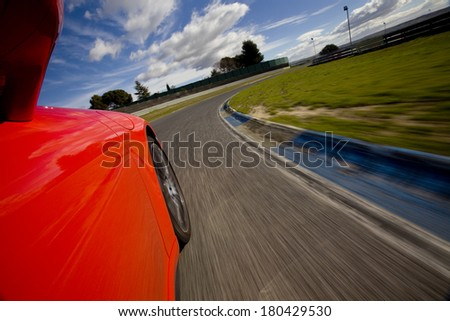 Low angle shot from the side of a car driving in a curve in a racetrack. Red car running in a racetrack. - stock photo