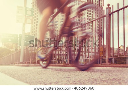 Low angle shot of a biker on riding on Brooklyn Bridge, Manhattan New York. Urban living, lifestyle, fitness and transportation  concept. Sun flare added - stock photo