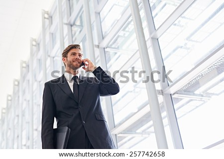 Low angle shot of a corporate executive walking along a modern corridor talking on his mobile phone - stock photo
