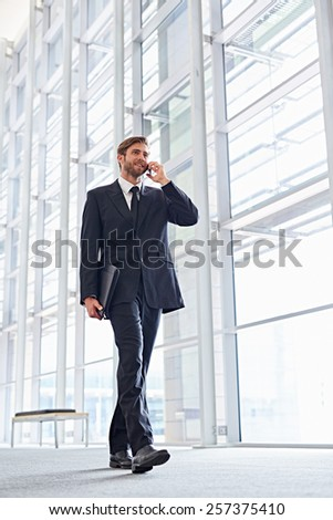 Low angle shot of a corporate executive walking while talking on his mobile phone - stock photo