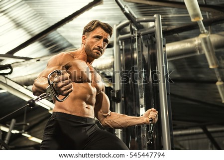 Low angle shot of a handsome mature athletic man with perfectly shaped toned muscular body working out at the gym doing chest exercises on cable crossover machine motivation health strength sport